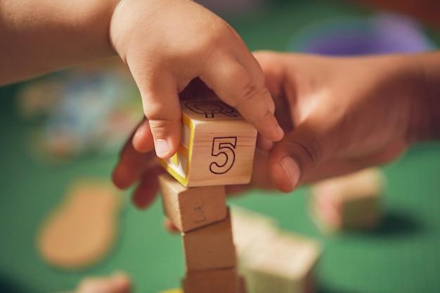 Mão da criança pegando um bloco de madeira com o número 5