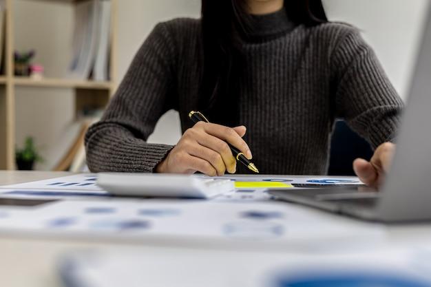Mão da empresária de close-up segurando uma caneta apontando para um gráfico de barras em uma folha de informações financeiras corporativas, a empresária examina as informações financeiras fornecidas pelo departamento financeiro.
