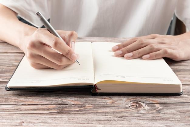 Mão da empresária escrevendo no papel no escritório