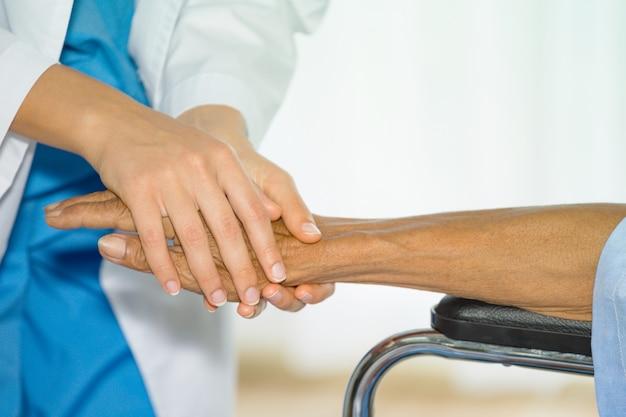 Mão da enfermeira fêmea que tranquiliza seu paciente do homem superior na cadeira de rodas na sala paciente no hospital.