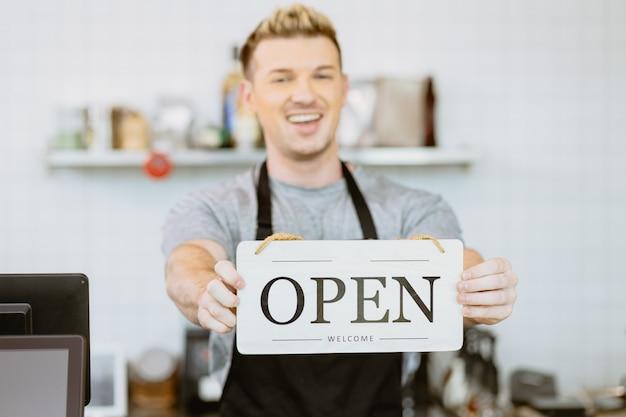 Mão da equipe do café barista café segurando a faixa de sinalização de abertura da loja, restaurante reaberto após conceito de bloqueio da covid