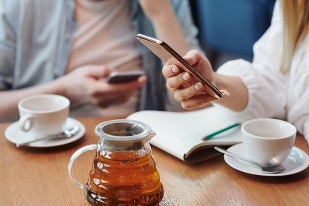 Mão da fêmea millennial scrolling no smartphone sobre a mesa enquanto toma uma xícara de chá no café com o namorado ou colega de grupo