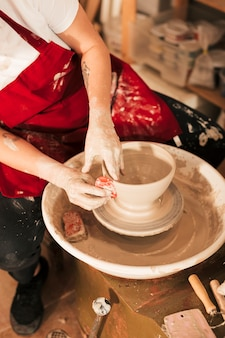Mão da fêmea, suavizando a tigela com ferramenta plana na roda de oleiro