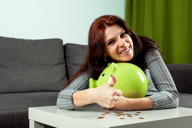 Mão da garota close-up, joga uma moeda para o cofrinho na forma de um porco verde