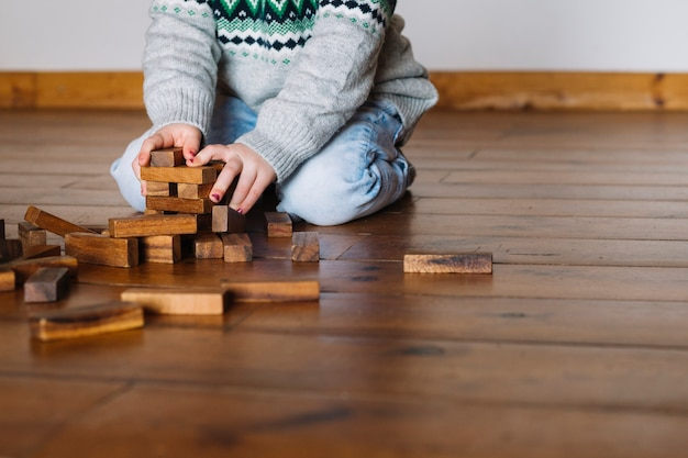 Mão da garota, construindo blocos de madeira