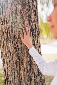 Mão da garota tocando a casca da árvore com a mão