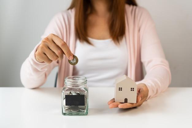 Mão da jovem mulher asiática colocando moedas no frasco de vidro. economizando, colete dinheiro para o conceito futuro.