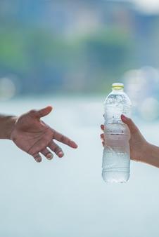 Mão da jovem mulher que dá ou que serve uma garrafa da água potável fria fresca a um homem após o exercício da aptidão.