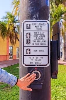 Mão da jovem mulher que empurra o botão para o sinal. use semáforos no cruzamento.