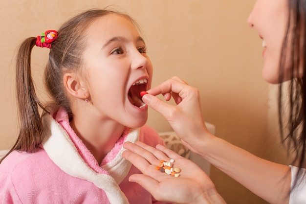 Mão da mãe colocando um comprimido na boca para a menina
