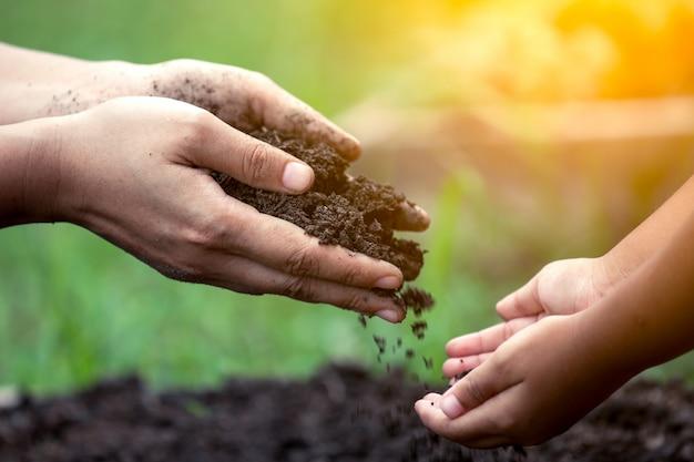 Mão da mãe dando solo para uma criança para o plantio juntos em tom de cor vintage