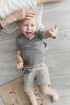 Mão da mãe na testa do filho deitado no chão de madeira, levantando a mão