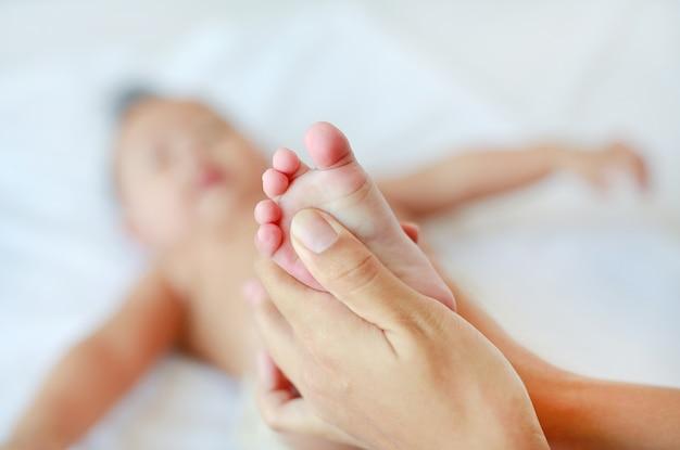 Mão da mãe que faz massagens os pés do bebê infantil na cama em casa.