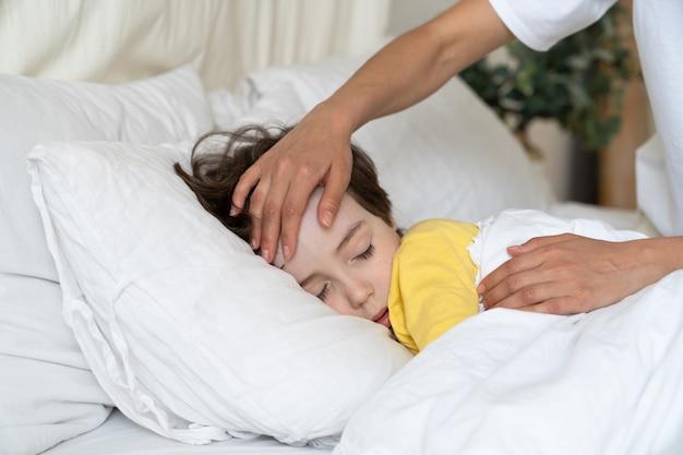 Mão da mãe tocando a testa do menino verificar a temperatura do filho doente dormindo na cama com febre de gripe