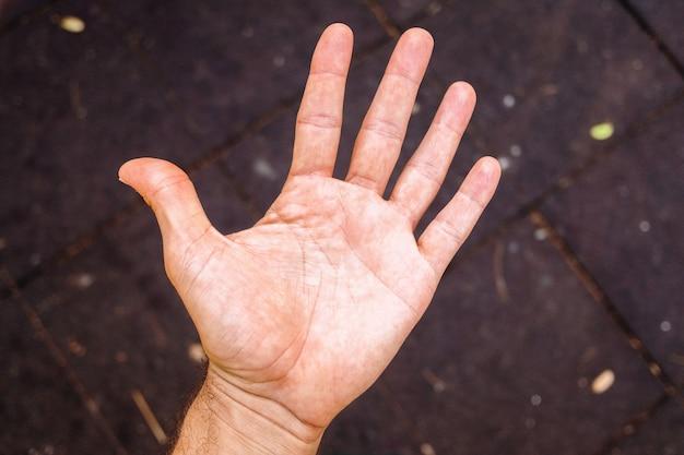 Mão da mão do homem pequeno, aberta e superior, isolada no fundo preto.