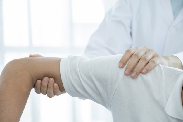 Mão da médica fazendo fisioterapia, estendendo o ombro de um paciente do sexo masculino.