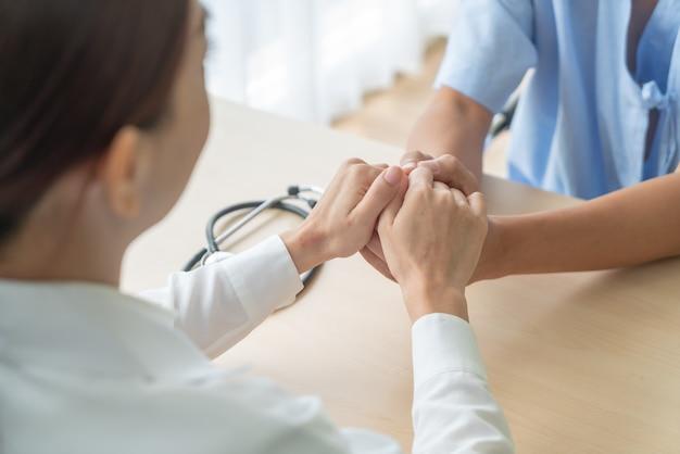 Mão da médica segurando seu paciente sênior