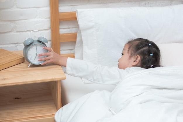 Mão da menina asiática que alcanga para desligar o despertador na cama na manhã