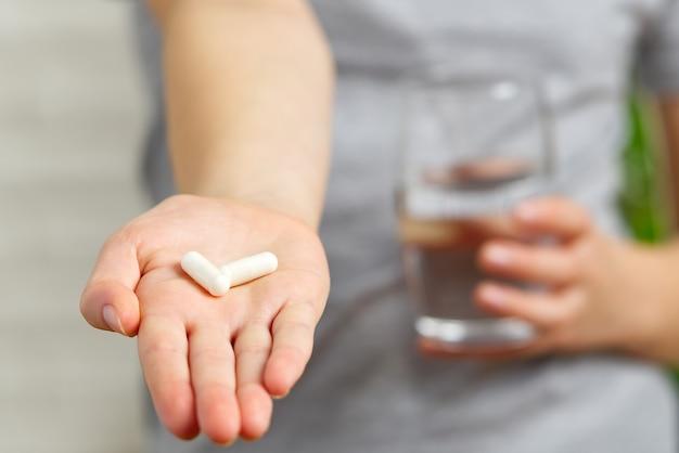 Mão da menina com comprimidos brancos, comprimidos, comprimidos e um copo de água