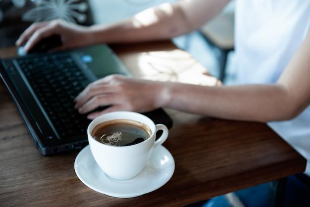 Mão da menina de escritório no teclado e no rato do portátil.