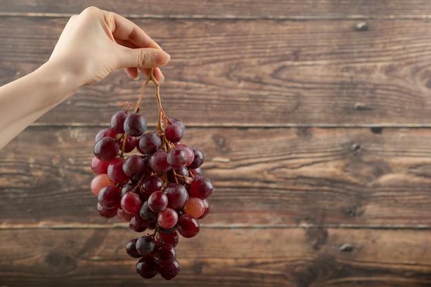 Mão da menina segurando cacho de uvas vermelhas na madeira.
