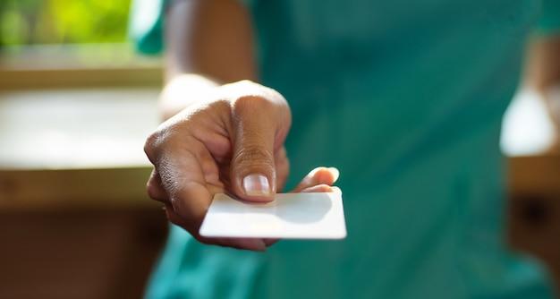 Mão da menina segurando um cartão de crédito