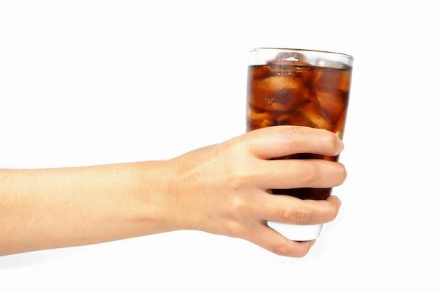 Mão da menina segurando um copo de coca-cola com gelo