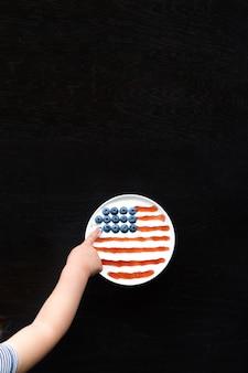 Mão da menina tocando uma baga da tigela com iogurte, mirtilos e geléia, dispostas na bandeira americana