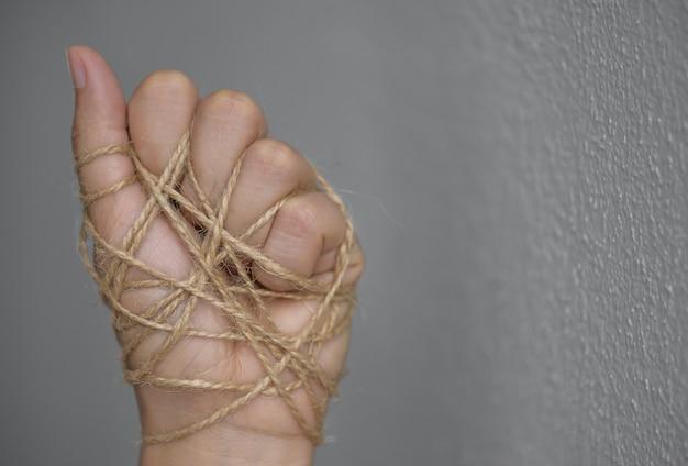 Mão da mulher amarrada com fio para o conceito do dia dos direitos humanos.