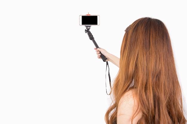Mão da mulher asiática que guarda o smartphone com a vara do selfie isolada no branco; copyspace.