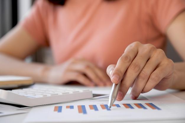 Mão da mulher asiática segurando a caneta, analisando o gráfico com a calculadora e o laptop no escritório em casa para definir metas de negócios desafiadoras
