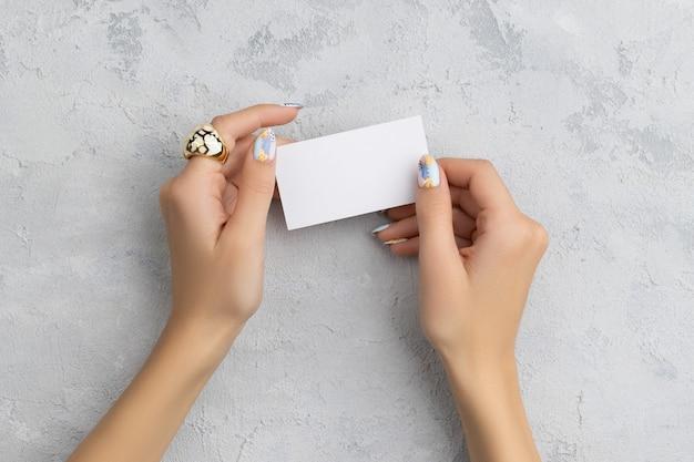 Mão da mulher bem cuidada segurando o cartão postal no fundo cinza de concreto. modelo de simulação de cartão de chamada simples.