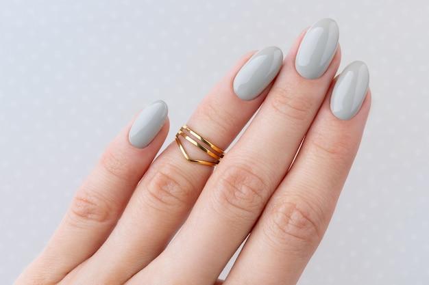 Mão da mulher bonita com manicure close-up no fundo de bolinhas