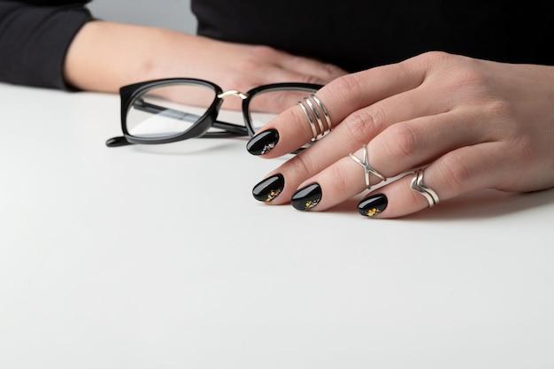 Mão da mulher bonita com manicure elegante. design de unhas preto mínimo