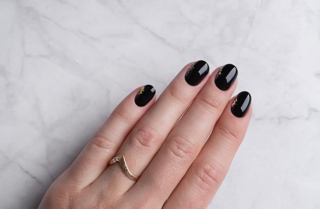 Mão da mulher bonita com manicure elegante em fundo de mármore. design de unhas preto mínimo.