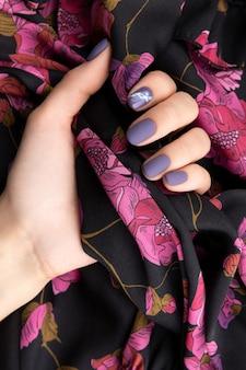 Mão da mulher bonita com manicure roxo fosco segurando tecido.
