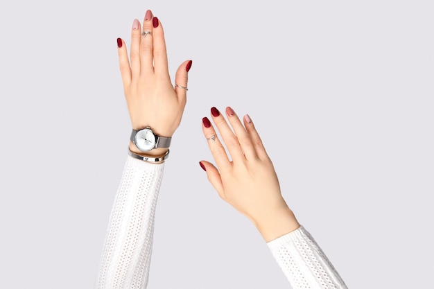 Mão da mulher bonita com uma manicure rosa em estilo minimalista. desenho de unhas de primavera de verão. conceito de produto de joias de prata para acessórios de moda