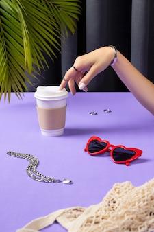 Mão da mulher bonita preparada com xícara de café de papel. acessórios femininos de verão