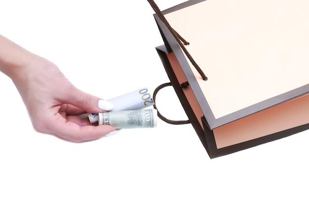 Mão da mulher colocando dinheiro em um saco de papel. isolado no branco. o conceito de gastos excessivos.