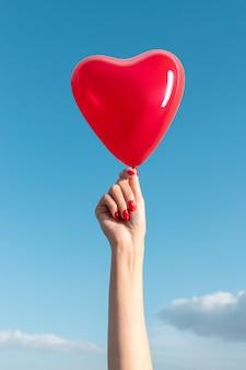 Mão da mulher com balão em forma de coração no fundo do céu.