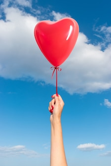 Mão da mulher com balão em forma de coração no fundo do céu
