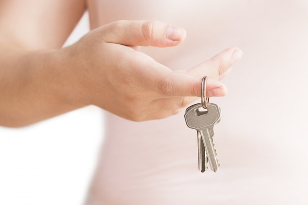 Mão da mulher com chave de metal. chaves à disposicão no fundo branco. isolado no branco