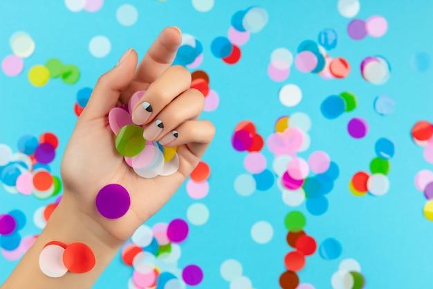 Mão da mulher com confetes coloridos sobre fundo azul. conceito de salão de beleza, moda e spa