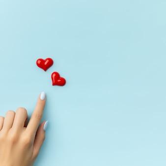 Mão da mulher com corações na superfície azul. desenho de unhas de verão