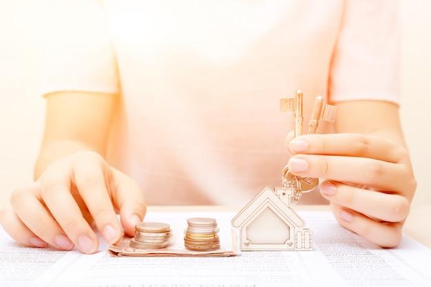 Mão da mulher com dinheiro e tecla home. contrato assinado e chaves da propriedade com documentos. conceito para negócios imobiliários.