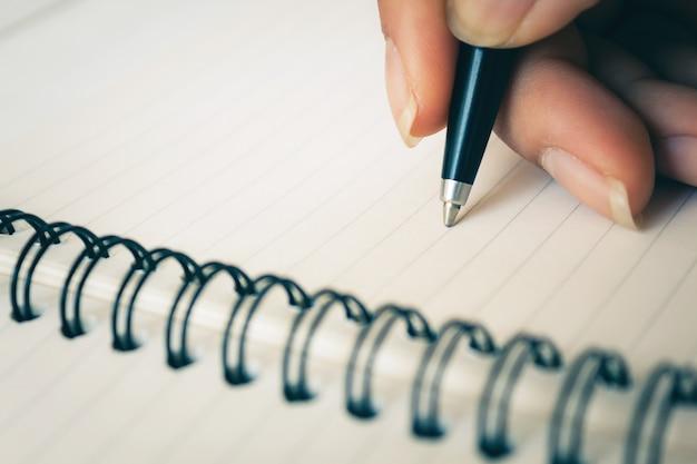 Mão da mulher com escrita da pena no caderno branco.