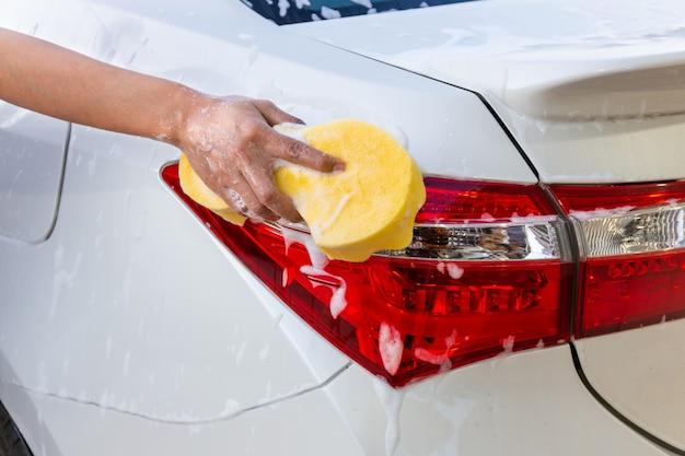 Mão da mulher com esponja amarela que lava o carro moderno da lanterna traseira ou que limpa o automóvel.