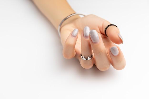 Mão da mulher com manicure crescida em fundo branco com espaço de cópia