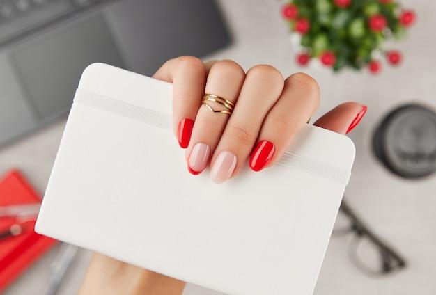 Mão da mulher com manicure da moda segurando o bloco de notas sobre a mesa, tendências de design de manicure