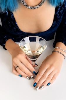 Mão da mulher com manicure segurando um copo de fundo vermute. design de unhas de prata noite escura festa.